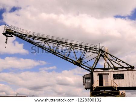 Old Vintage Wooden Port Crane on a Cloudy Blue Sky