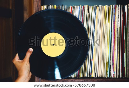 Old vinyl record and a collection of albums. #578657308