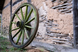 Old wagon wheel leaning up against an old historic rustic mud or daub and timber frame building with weathered walls and exposed wood framework in a closeup view