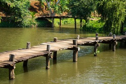 Old walking wooden bridge on lake