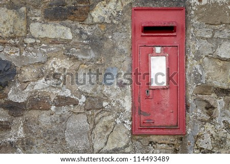 Old wall made of rocks and stones with red postbox, texture background