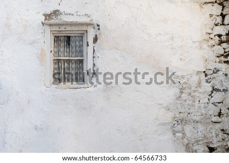 Old wall with a window with curtain shattered. Background. Texture