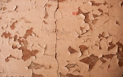 Old wall with peeling layers of paint and cracks close up