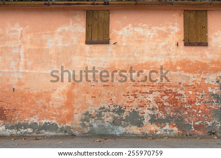 old wall with peeling paint, scratched stained plaster and closed windows - grunge background of urban decay   #255970759