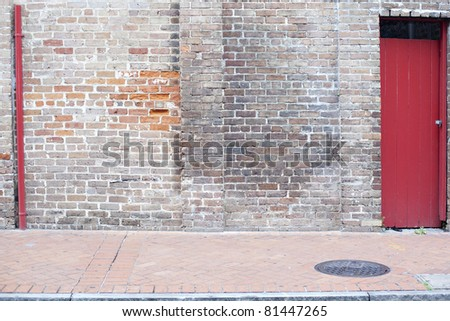 old wall with red door brick sidewalk background
