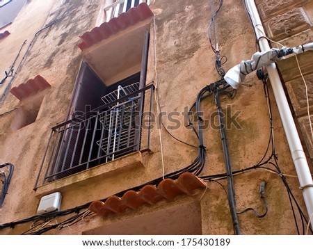 Old wall with window, clothes dryer and old cables on it