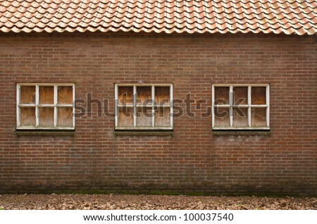 Old wall with windows, windows have been covered with wooden panels