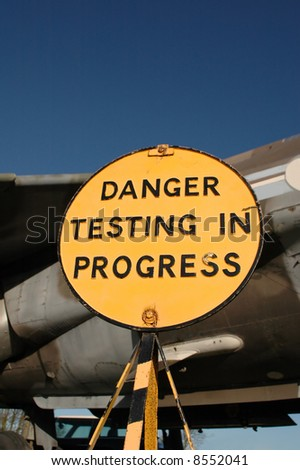 old warning sign next to vintage military jet - stock photo