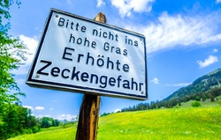 old warning sign of ticks in germany - translation: beware of ticks in the high grass