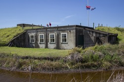 Old wartime bunker nestled in hillside beside creek with two people. Fort Lytton, Brisbane, Queensland, Australia.