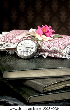 Old watch and books on vintage suitcase