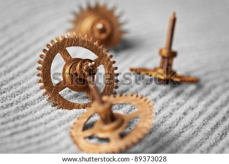 Old watch gears on the gray sand - abstract still life