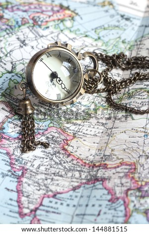 Old watch with sphere surface on antique map