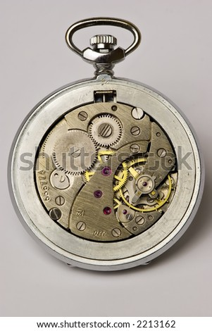 Old watch with the bottom taken off, mechanism is visible and all gears that match each other are visible, it\'s a symbol of perfect teamwork
