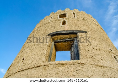 Old Watchtower of an old fortress rising up to the sky - shot from below. From Muscat, Oman.