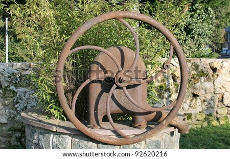 old water pump has become a decorative item in a city: symbol of the past - stock photo