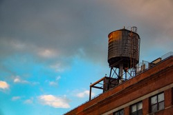 old water tank tower over building in nyc new yor city with cloudy sky
