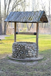 old water well with roof standing in garden