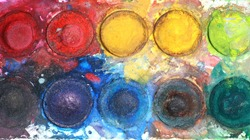 Old watercolor tray mixed with dust, close up,top view.