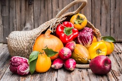 Old wattled bag full of colorful fresh autumn vegetables and fruits