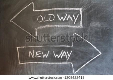 Old way, new way written on chalkboard. Change concept