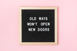 Old Ways Won't Open New Doors. Motivational quote on black letter board on pink background. Concept inspirational quote of the day. Greeting card, postcard.