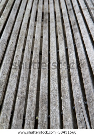 Old weathered and worn curved wood bench