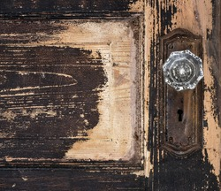 Old weathered antique beat-up wood panel door with chipped peeling paint, textured, and glass crystal doorknob and rusted plate