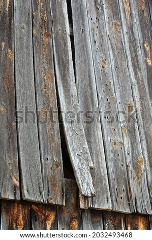 Old weathered barn exterior featuring rough textured, warped and weathered barn boards with one coming unattached at the bottom. Boards are held in place by rusty nails. Stockfoto ©