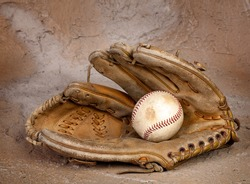 Old weathered baseball glove against a grungy background