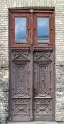 Old weathered beautiful doors. Wood carving. Wooden texture. Figure cutting on wood. Interior Retro Background. Traditional carved wooden doorway.