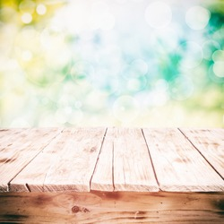 Old weathered cracked wooden table in a sunny summer garden with a high key background, low angle with space for product placement