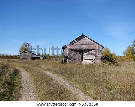 old weathered farm building on road