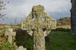 Old Weathered Granite Celtic Cross Gravestone Covered in Moss and Lichens in the Graveyard of a Church on the Island of Tresco in the Isles of Scilly, England, UK