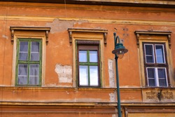 Old weathered orange brown colour vintage building detail with windows and a traditional metal street lamp in fornt of the house in Budapest downtown, Hungary
