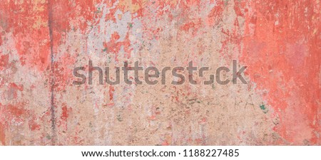 Old weathered painted wall background texture. Red dirty peeled plaster wall with falling off flakes of paint.
