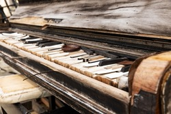 Old weathered piano close up on black and white keys