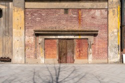 Old weathered rusty factory gate and the dated brown brick wall in the sunlight