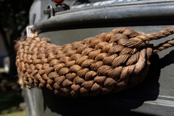 Old weathered ship woven rope fender hanging on side of old military ship