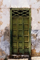 Old weathered traditional green painted door in canarian colonial style house in the old town of Santa Cruz de La Palma, in the quarter of San Sebastian, also known as La Canela