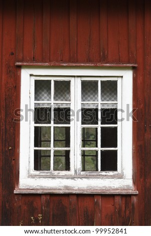 old weathered window at a red house