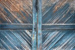 old weathered wood panel door peeling blue paint bare wood diagonal pattern textured