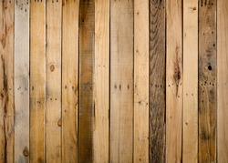 Old weathered wood surface with long boards lined up. Wooden planks on a wall or floor with grain and texture. Dark natural brown tones with contrast.