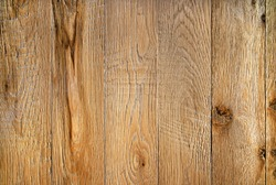 Old weathered wood surface with long boards lined up. Wooden planks on a wall or floor with grain and texture. Warm brown and orange tones.