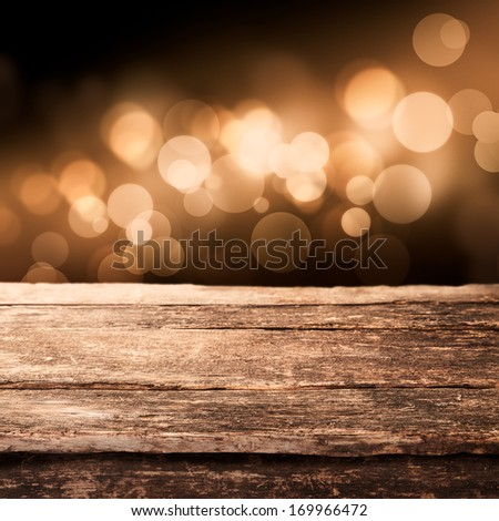 Old Weathered Wooden Board Or Rustic Table Top With A Sparkling Bokeh Of Golden Party Lights In The Background