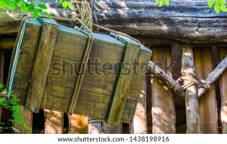 Old weathered wooden box hanging on a rope, medieval lifting methods, shipping and harbor background