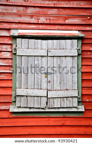 Old weathered wooden shuttered window on a red wall locked