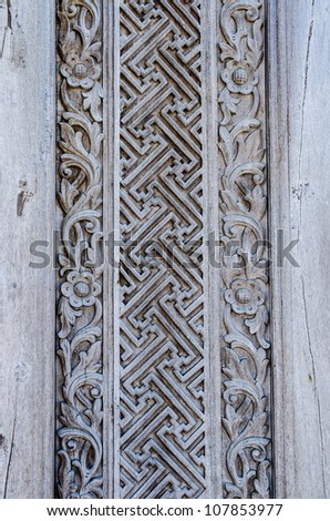 Old weathered wooden wall decoration with carved ornament