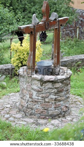 Old Well with a bucket and a horseshoe. Made of stone and wood