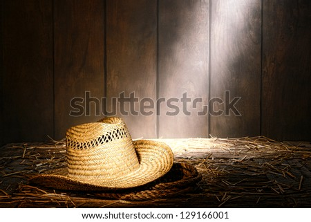 Old West farmer straw hat atop a sisal ranching rope on hay covered antique wood floor in a dusty vintage ranch hay barn lit by diffused sunlight